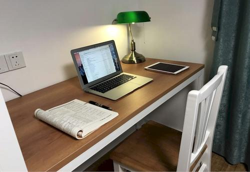 Wooden desk and chair with Macbook Air, iPad, pen, booklet and lamp