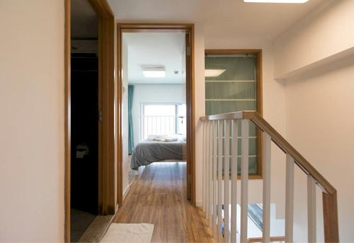 Hallway with wooden floor, bedroom and stairs