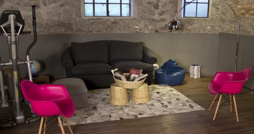 Comfortable sofa and pink chairs with basket table containing magazines