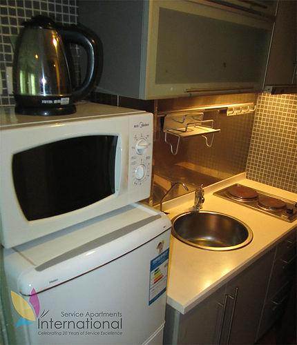 Kitchen with microwave, refrigerator, and kettle