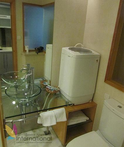 Bathroom with big mirror, washing machine, and glass sink