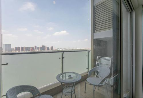 Balcony with chairs, table, and view of the city skyline at day