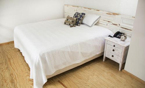 King-size bed with high-quality linen, soft pillows, and bedside table with telephone and clock