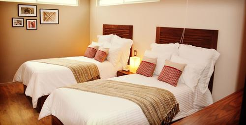 Twin beds with soft pillows, high-quality bedding set, bedside table with telephone and lamp