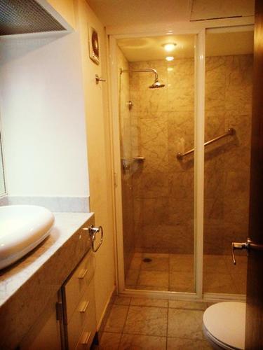 A spacious bathroom with rainforest shower head