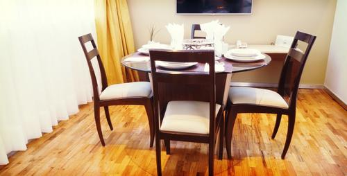 Wooden dining table with four soft, high-quilty chairs