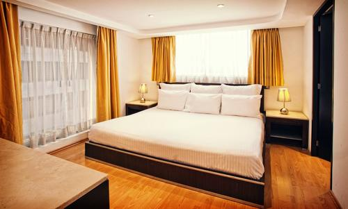 King-size bed with linen, soft pillows, bedside tables with lamps