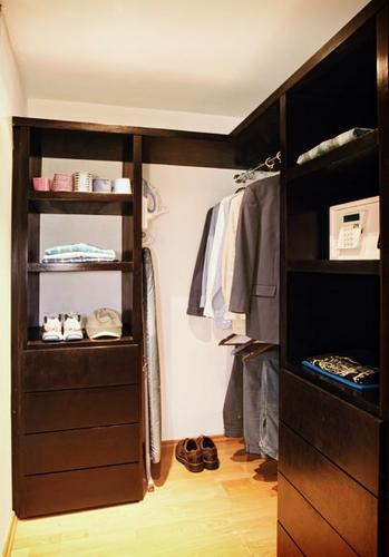 A spacious wardrobe with drawers, safe, ironing board an iron