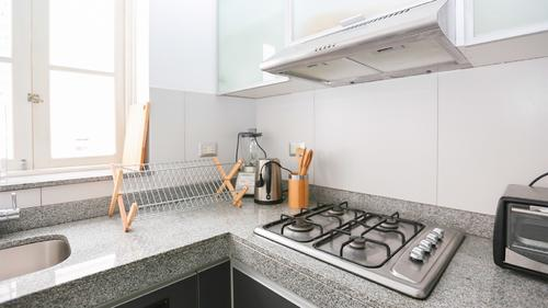Fully equipped kitchen with a stove, and hood