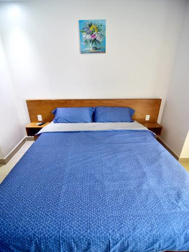 Comfortable bed with a blue bedding set and pillows